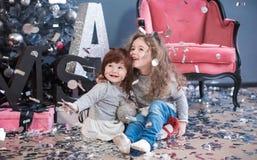 Les enfants jettent des confettis et s'asseyent sur un plancher près d'un sapin photographie stock