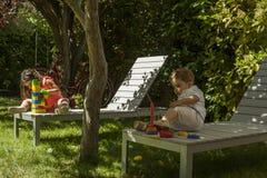 Les enfants jouant avec la construction joue dans le jardin Image stock