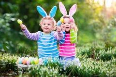 Les enfants jouant avec le busket d'oeufs sur l'oeuf de pâques chassent Photos stock