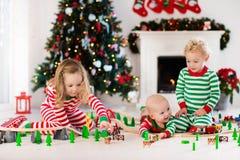 Les enfants jouant avec le jouet railroad le matin de Noël Images libres de droits