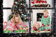 Les enfants jouant avec le jouet railroad le matin de Noël Images stock