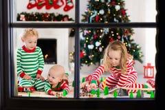 Les enfants jouant avec le jouet railroad le matin de Noël Photo stock