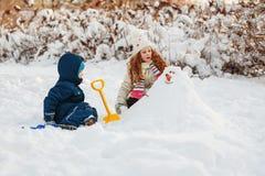 Les enfants jouant avec un bonhomme de neige un hiver marchent en parc Photo stock