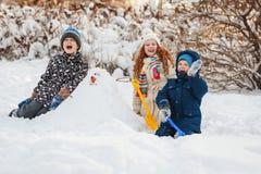 Les enfants jouant avec un bonhomme de neige un hiver marchent en parc Photographie stock libre de droits