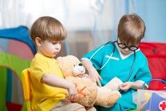 Les enfants jouant le docteur et traitant la peluche jouent à la maison photos stock