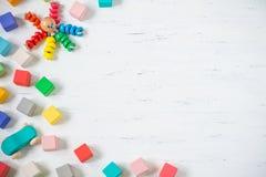 Les enfants joue les blocs en bois de cadre, le poulpe, voiture sur le fond en bois blanc Configuration plate Copiez l'espace pou Image stock