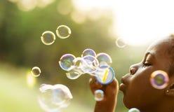 Les enfants joue des bulles en parc Photos libres de droits
