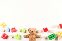 Les enfants joue le fond avec l'ours de nounours et les blocs colorés Photo libre de droits