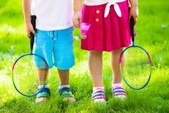 Les enfants jouent au badminton ou au tennis dans la cour extérieure Image libre de droits