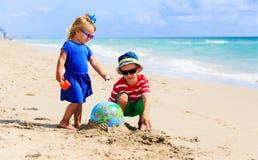 Les enfants jouent avec l'avion de globe et de jouet sur la plage, concept de voyage Photos stock