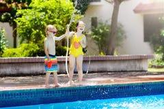 Les enfants jouent avec le tuyau de l'eau à la piscine Image stock