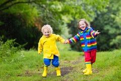 Les enfants jouent dans la pluie et le magma en automne Image stock