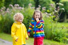 Les enfants jouent dans la pluie et le magma en automne Photo stock