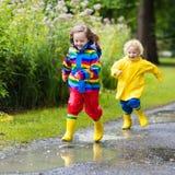Les enfants jouent dans la pluie et le magma en automne Photos stock