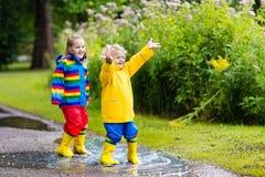 Les enfants jouent dans la pluie et le magma en automne Images stock