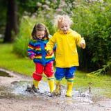 Les enfants jouent dans la pluie et le magma en automne Photographie stock libre de droits