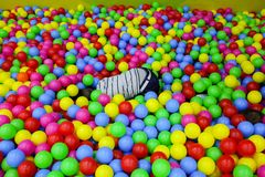 Les enfants jouent dans le puits de boule avec les boules en plastique color?es chez le centre de divertissement des enfants Mett image stock