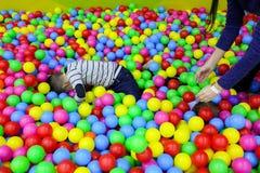 Les enfants jouent dans le puits de boule avec les boules en plastique color?es chez le centre de divertissement des enfants Mett photo libre de droits