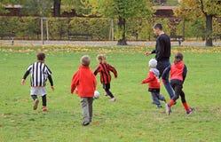 Les enfants jouent le football en parc de ville Photographie stock libre de droits