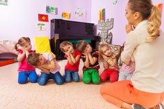 Les enfants jouent le jeu feignant soient endormis avec le professeur Images libres de droits