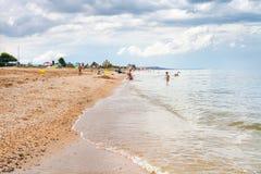 Les enfants jouent sur le sable et la mer de plage d'Azov coquillière Photos stock