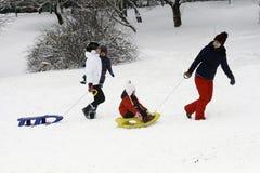 Les enfants joyeux sledding vers le bas Photographie stock libre de droits