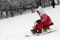 Les enfants joyeux sledding vers le bas Images stock