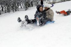 Les enfants joyeux sledding vers le bas Photographie stock