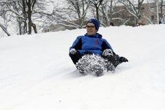 Les enfants joyeux sledding vers le bas Images libres de droits