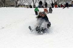 Les enfants joyeux sledding vers le bas Photo stock