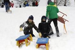 Les enfants joyeux sledding vers le bas Photos libres de droits