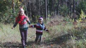 Les enfants, le frère et la soeur heureux courent par la forêt en automne banque de vidéos