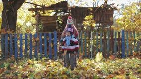 Les enfants, le frère et la soeur ruraux et drôles jettent des feuilles d'automne clips vidéos