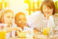Les enfants mangent de la céréale au petit déjeuner dans la colonie de vacances Photos libres de droits