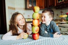 Les enfants mangent des pommes et ont l'amusement dans la cuisine au matin Images libres de droits