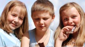 Les enfants mangent du chocolat. Image stock