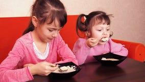 Les enfants mangent du gruau Deux petites filles mangent du gruau Deux soeurs s'asseyant sur le divan et le dîner oranges clips vidéos