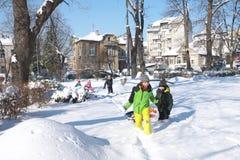 Les enfants marchant dans la rue se sont recroquevillés avec la neige Images libres de droits