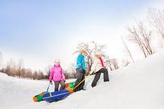 Les enfants marchant vers le haut de la colline neigeuse et portent des tubes Photo libre de droits