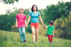 Les enfants marchent avec leur mère à travers le champ Photographie stock