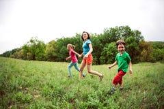 Les enfants marchent avec leur mère à travers le champ Image stock