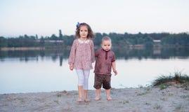 Les enfants marchent ensemble sur la banque du lac Promenade active de famille photos stock