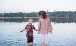 Les enfants marchent ensemble sur la banque du lac Promenade active de famille images libres de droits