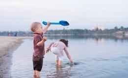 Les enfants marchent ensemble sur la banque du lac Promenade active de famille photographie stock
