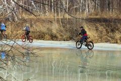 Les enfants montent des bicyclettes sur la glace de la rivière au printemps Images stock
