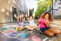Les enfants montrent des paumes colorées dans le jeu de dessin de craie Images libres de droits