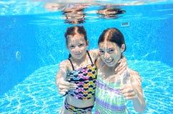 Les enfants nagent dans la piscine sous-marine, les filles actives heureuses ont l'amusement sous l'eau Images libres de droits
