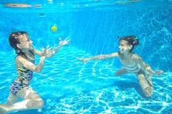 Les enfants nagent dans la piscine sous-marine, les filles actives heureuses ont l'amusement sous l'eau Photos stock
