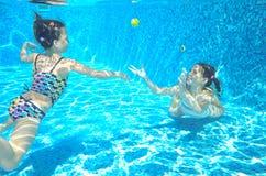 Les enfants nagent dans la piscine sous-marine, les filles actives heureuses ont l'amusement sous l'eau Photo stock