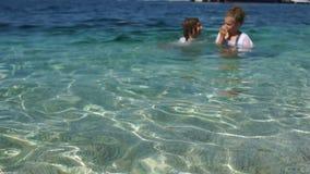 Les enfants nagent dans le juste d'eau de mer de turquoise dans leurs vêtements Bonnes fêtes avec des enfants concept de course clips vidéos